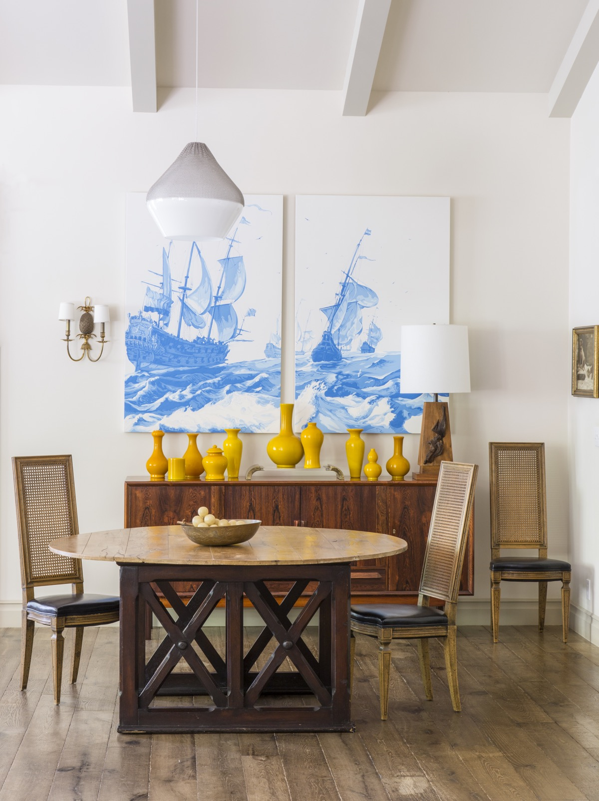 Wood dining table and chairs in light dinging area with hardwood floor, bowl with large grapes, wall hutch with various sized yellow ceramics, lamp, and wall painting.